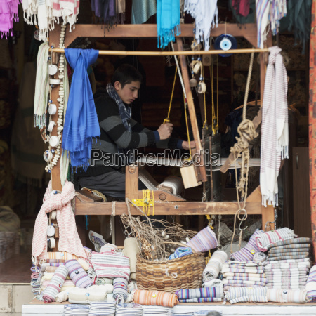 a young man works a loom