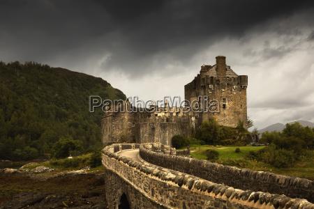 stone bridge leading to a castle