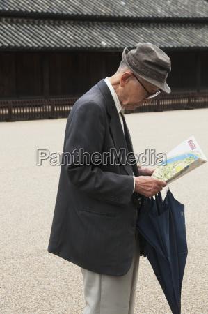 senior man looking at map tokyo