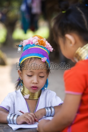young girls wearing neckrings and writing