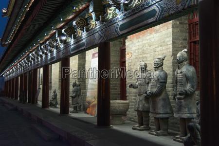 statues along the illuminated wall of