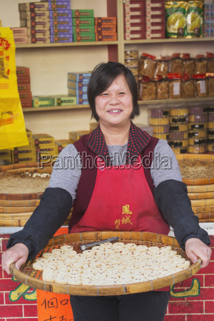 smiling woman holds tray of chinese