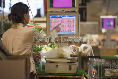 a cashier weighs fresh produce on