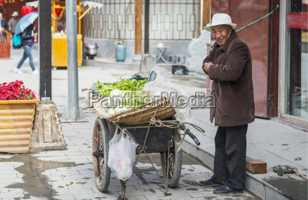 aged man sells vegetables on the