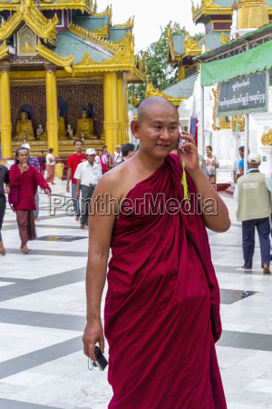 buddhist monk with camera talking on