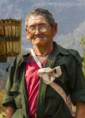 a bhutanese elderly male porter with
