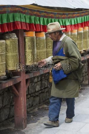 man walking along prayer wheels at