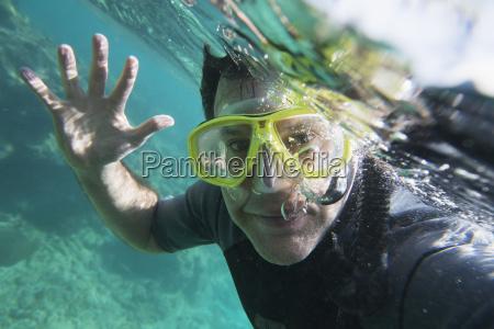 a male scuba diver waves hello