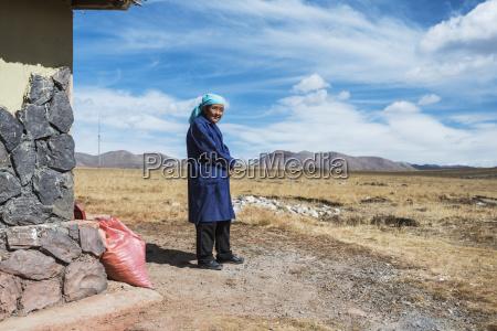 kind tibetan woman near her house