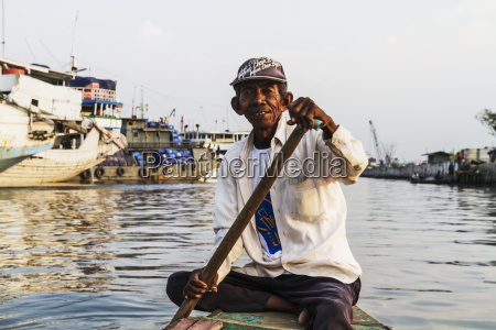 man rowing a boat in sunda