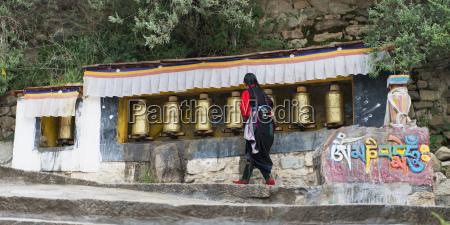 nun walks by prayer wheel at