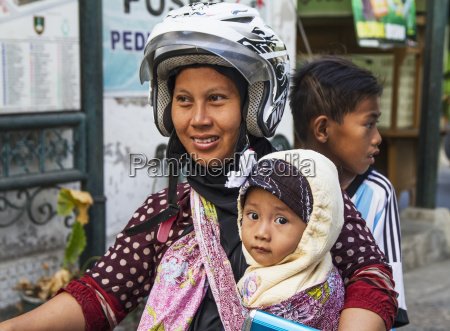 woman and children on a motorcycle