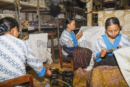 craftswomen drawing intricate patterns by using