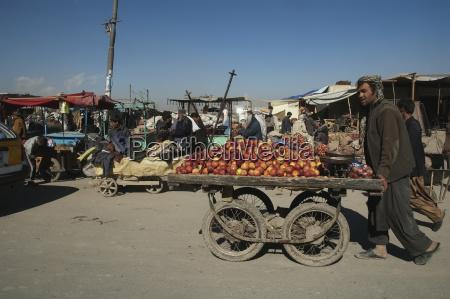 man pushing an apple laden cart