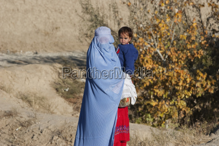 afghan woman wearing a burqa holding