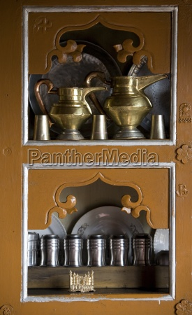 kitchen cupboards containing traditional jugs and