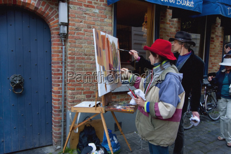 painters painting a street scene bruges