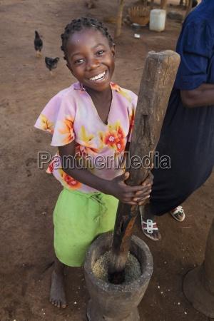 a girl pounding corn into flour