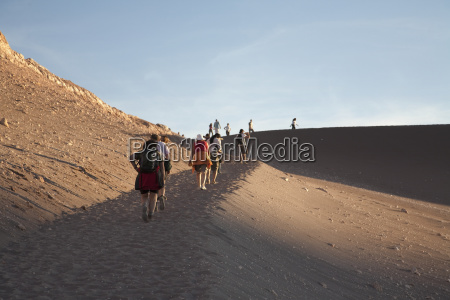 people climbing a sand dune in