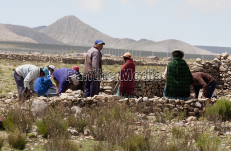 people building a pirca stone fence