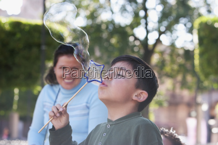 boy blowing soap bubbles at plaza