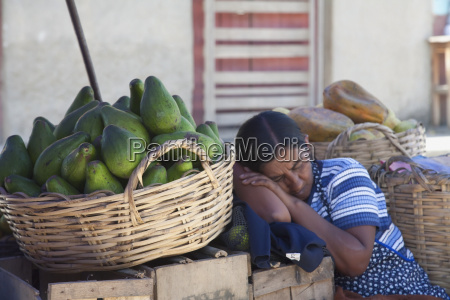 woman sleeping at her produce stand