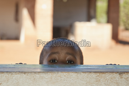 boy peeking through a window in