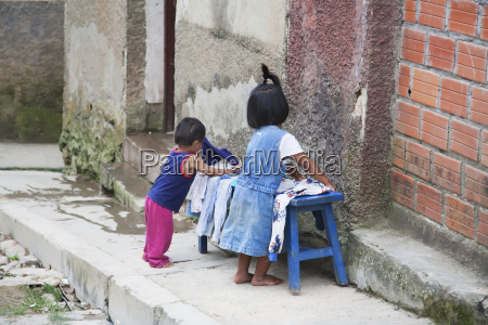 children putting clothes on a bench