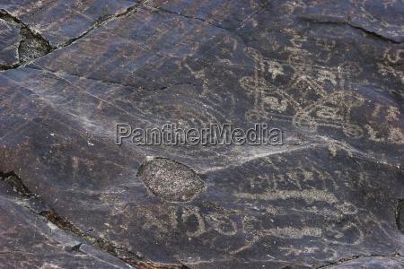 petroglyphs on a boulder show buddhist
