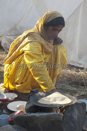 woman preparing breakfast outside a relief