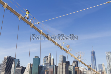 men painting a suspension cable of