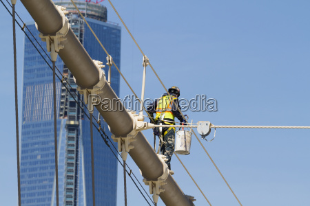 man painting a suspension cable of