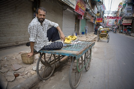 man selling bananas from cart in