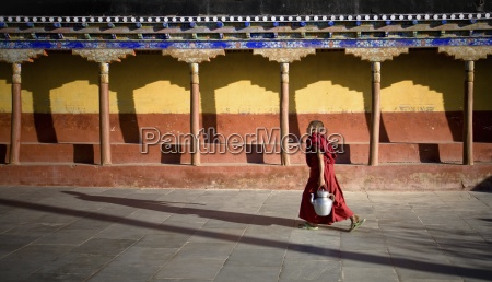 young buddhist student carrying teapot through