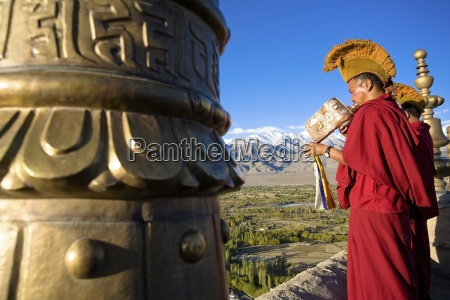 buddhist monk blowing conch shell trumpet