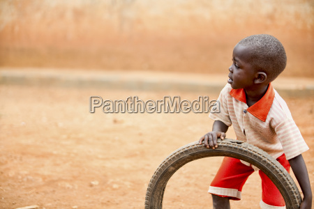 a boy plays with a tire
