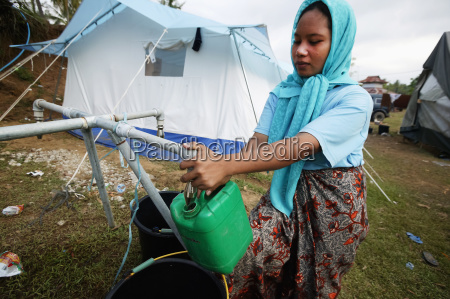 a woman collects water for home