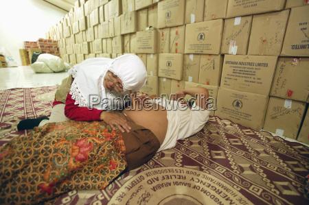an elderly muslim midwife checking a