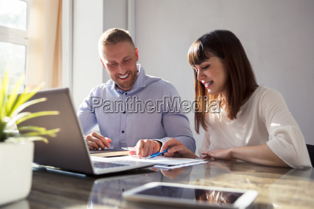 two businesspeople working on document
