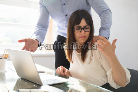 businessman touching shoulder of female colleague