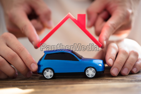 human hand protecting blue car
