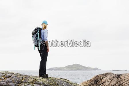 female hiker on rounded rocks overlooks