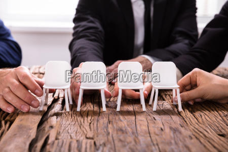 businesspersonss hands arranging chairs in a