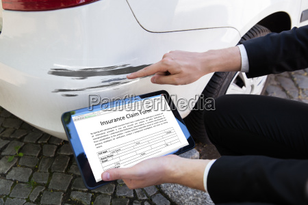 person examining damaged car while filling