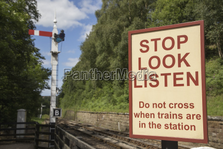 sign of caution along train tracks
