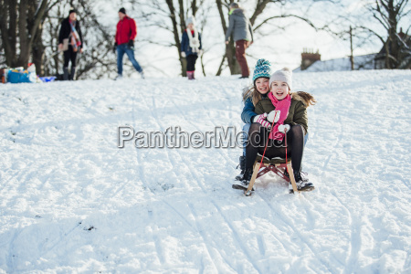 two girls sledding down the hill