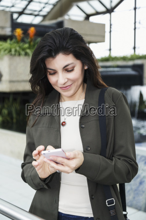 mature business woman texting while taking