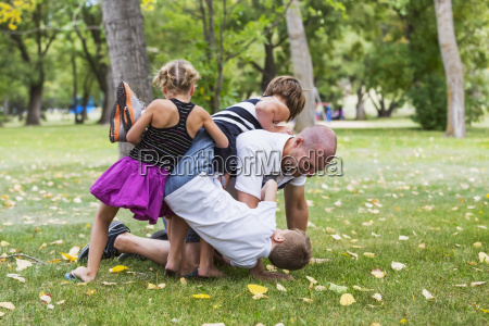 a father wrestling with his kids