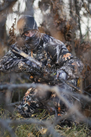 hunter ground stalking whitetail deer