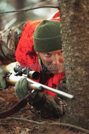 deer hunter stalking with rifle